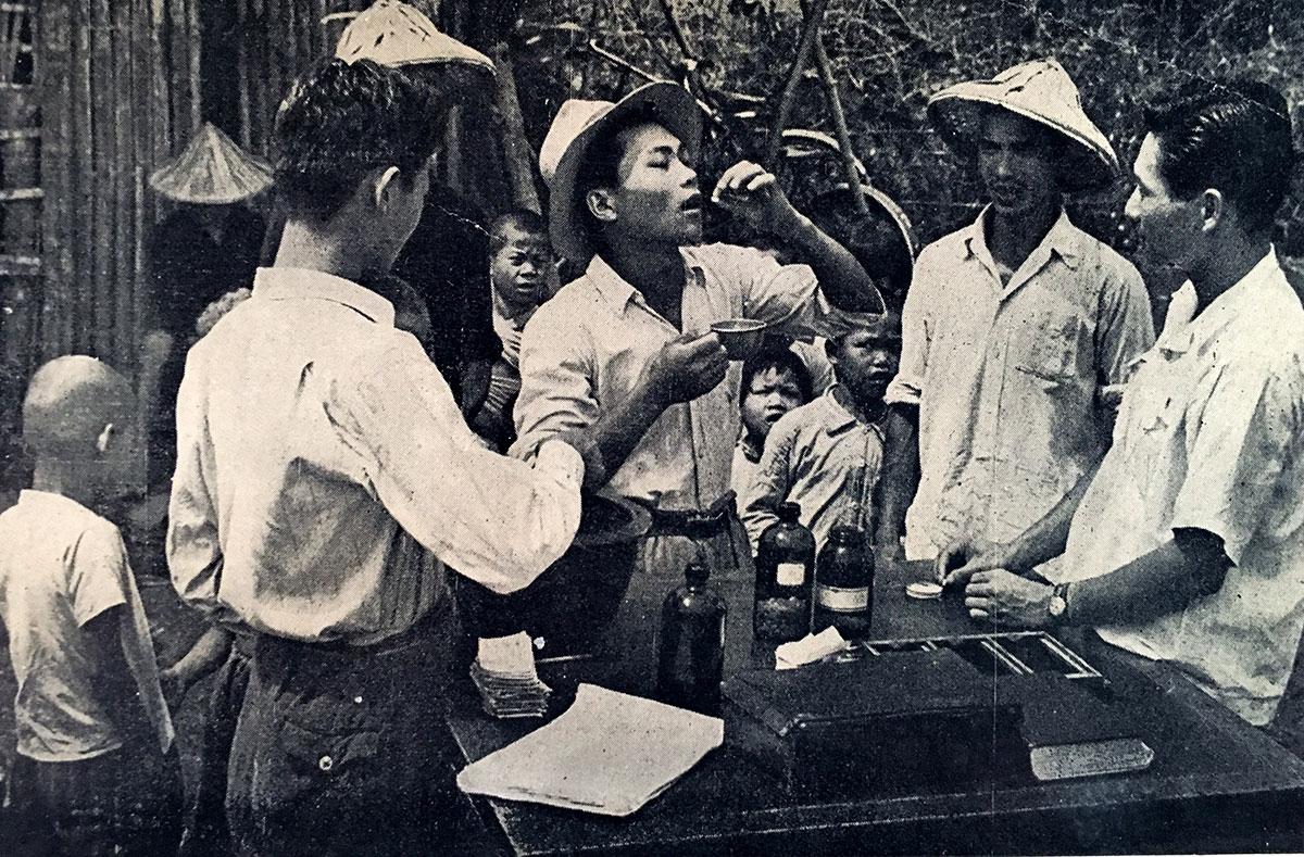 Ciutadans vietnamites ingereixen el tractament antimalàric.